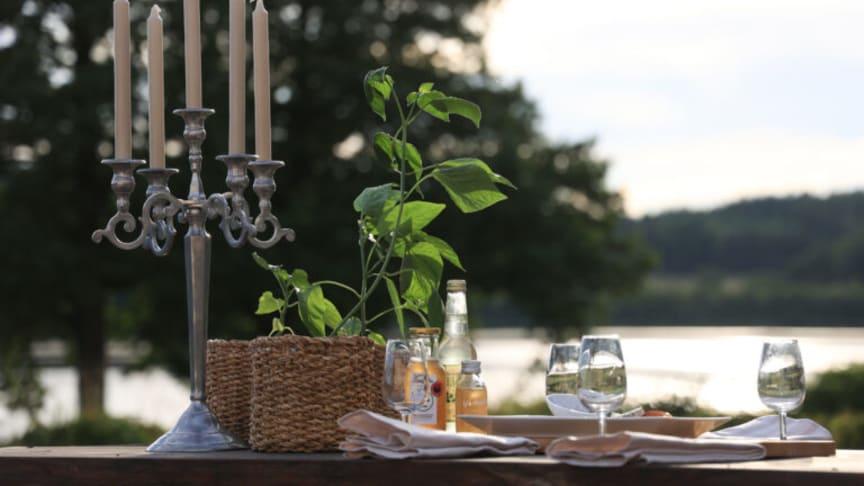 Dryckesglas på ett bord i naturen med en sjö i bakgrunden.