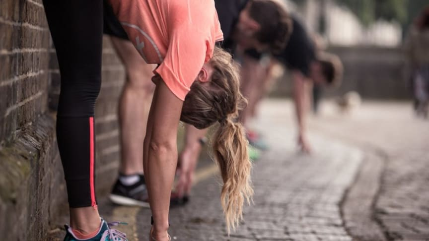 Woman in running gear stretching