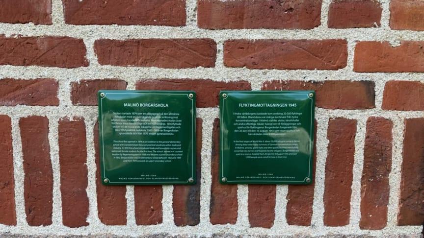 Två minnesskyltar vid huvudentrén på Borgarskolan