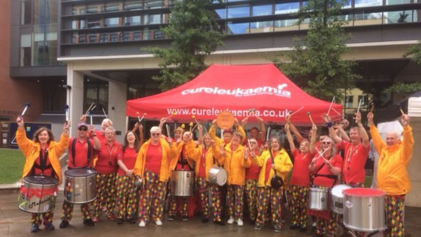 Someone at the Door Samba band playing in Brindley Place with their Cross City Heroes plaque