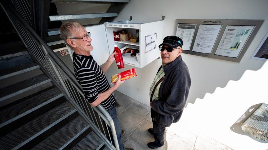 Grannarna Ingemar Olsson och Jan Jönsson visar exempel på varor som donerats till Grannskåpet.  Foto: Björn Lilja