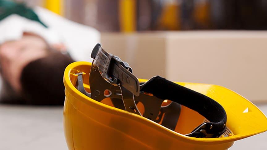Bilden visar en gul skyddshjälm i förgrunden samt en person liggande på ett golv i bakgrunden. Bild från AdobeStock.