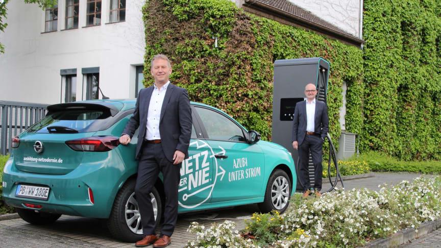 Zwei für Westfalen Weser wichtige Themen vereint: Jürgen Noch (v.) und Andreas Speith mit einem der beiden Elektroautos nur für Azubis.
