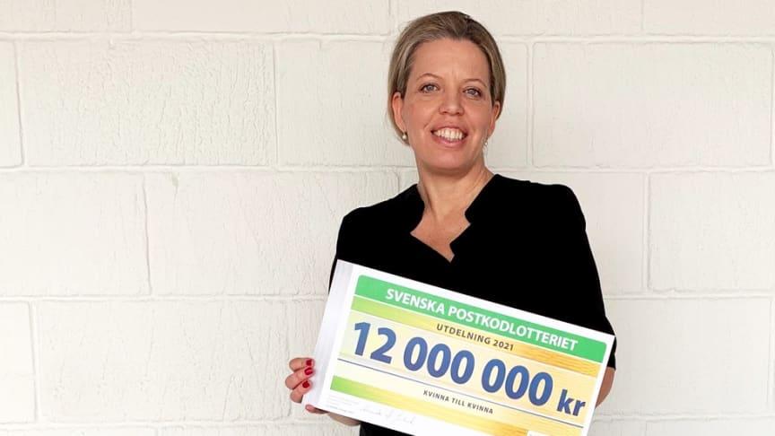 Kvinna till Kvinnas generalsekreterare Petra Tötterman Andorff mottar årets check från Postkodlotteriet på tolv miljoner kronor.