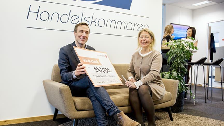 Oskar Axelsson, regionchef på Handelskammaren Mälardalen, tar emot checken på 100 000 kr från bankens VD Cecilia Jeffner.
