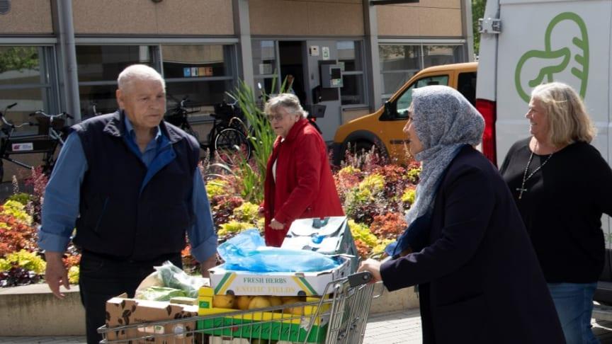 Glade modtagere i gang med at tømme FødevareBankens kølebil for overskudsvarer.