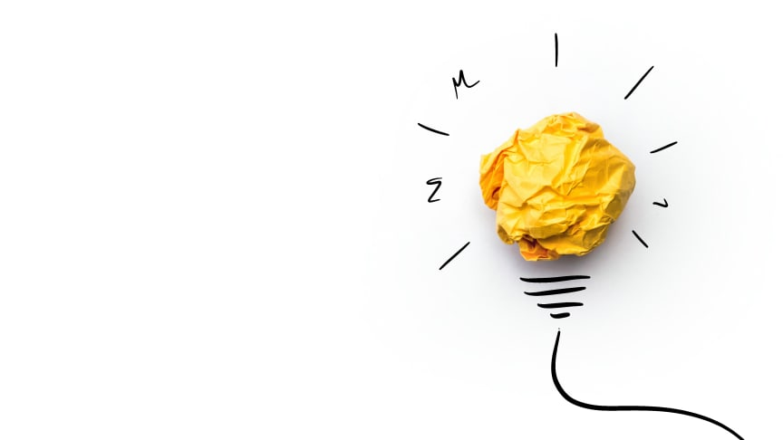 A yellow scrunched ball of paper forms the centre of an illustrated lightbulb against a white background. Royalty-free stock photo ID: 422864347.