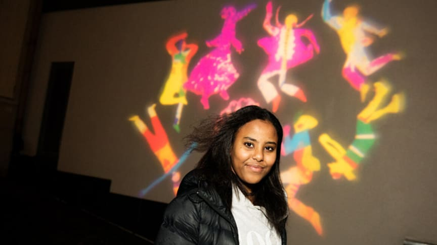 Eldana Simon 13 år, framför det konstverk hon varit med och skapat. Foto: Sara Appelgren.