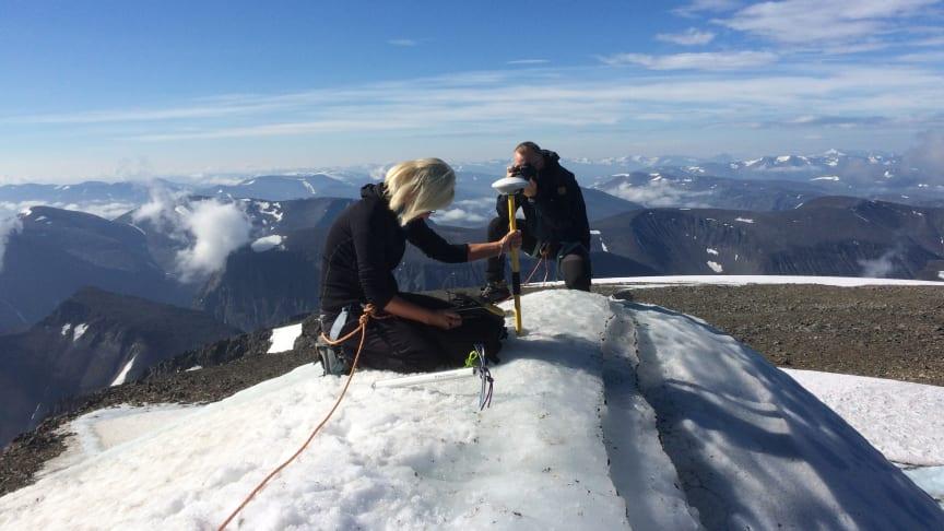 Forskaren Gunhild Ninis Rosqvist mäter höjden på sydtoppen av Kebnekaise som i juli år har minskat med fyra meter på grund av den rekordvarma sommaren.  Foto: Carl Lundberg