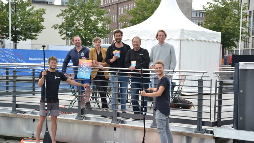 v.l. J. Hesse (Kiel-Marketing), N. Grenz (Deichperle), N. Grimm (Musikprogramm), R. Pasternak (Kulturreferent LH Kiel), F. Pape ( Alte Mu Impuls-W Kiel) v.l. auf den SUPs M. Krusenbaum (Surf Shop Kiel), F. Ehlers (Ocean Global Verlag)
