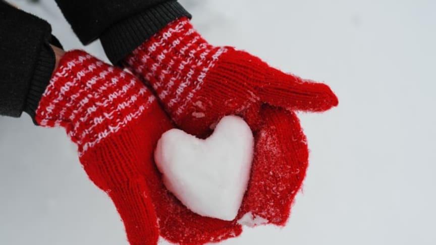 Händer i vantar som håller ett snöhjärta.