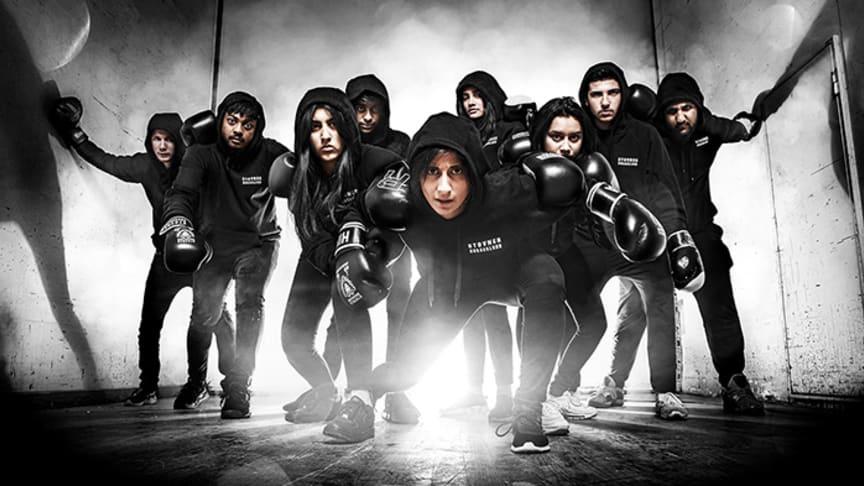 Ungdomar frå 14-18 år frå Stovner Bokseklubb står på scenen i lag med boksetrenar Hina Zaidi på Rommen Scene.