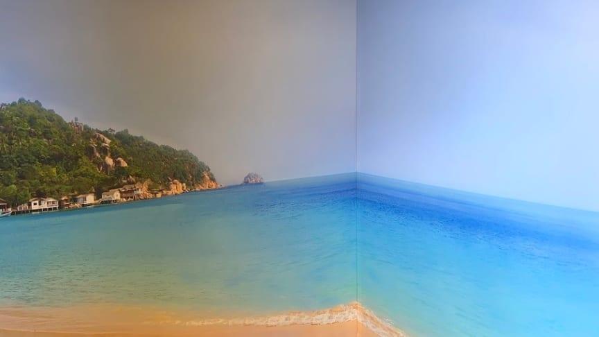 Köksskåp flyttades ut för att göra plats åt en stor fondbild med tropisk sandstrand som täcker två väggar och skapar en skön panorama-känsla.