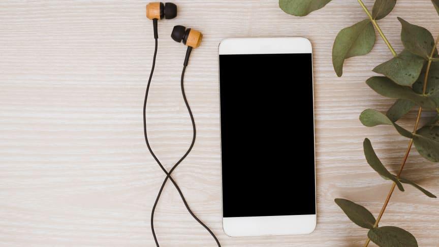 En mobiltelefon och hörlurar med gröna blad bredvid