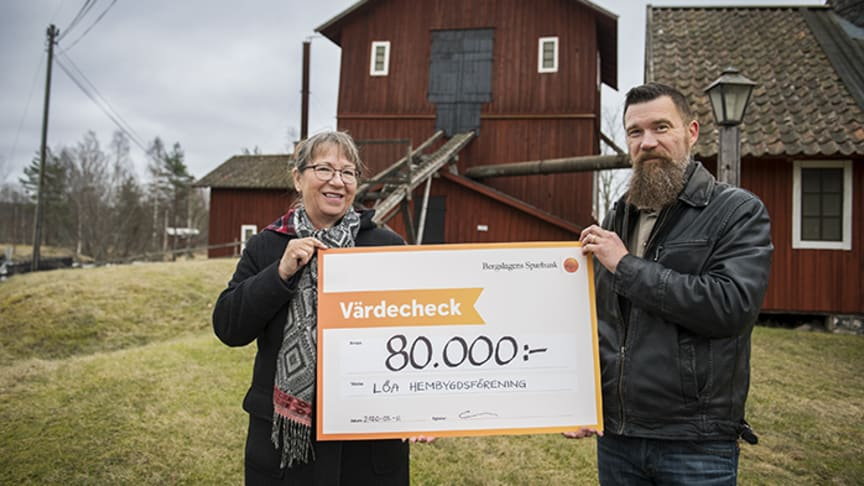 Eva Persson, projektledare för Hyttans hemligheter, tar emot check från Ola Anderberg, bankens kontorschef i Kopparberg.