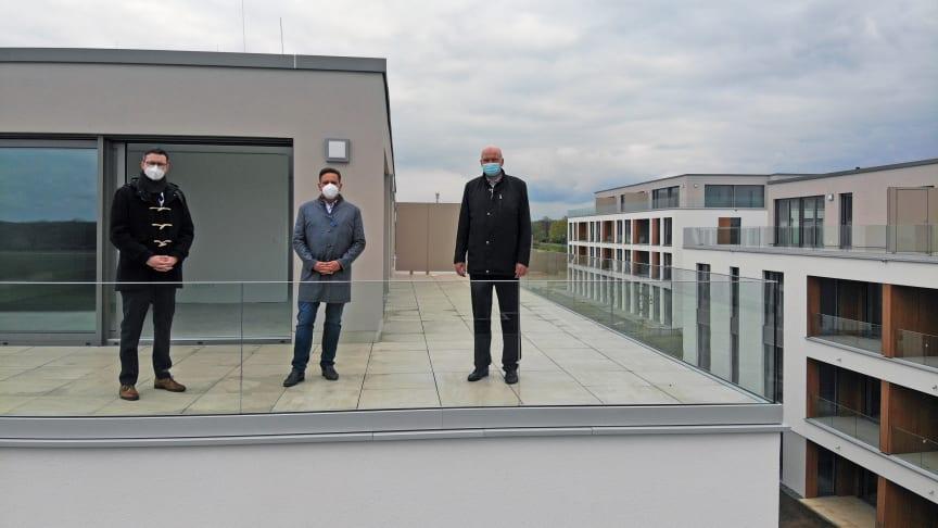 """(v.l.n.r.): Maximilian Bohr (Abteilungsleiter Individualkunden BS Energy), Thorsten Schmidt (Geschäftsführer Bauunternehmen Schmidt GmbH & Co.KG ) und Kai-Uwe Rothe (Geschäftsführer BS Netz) über den Dächern des Baugebietes """"Neue Mitte"""" in Lamme."""