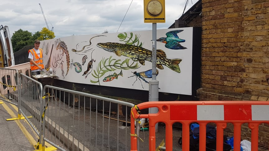 Mark Anthony of ATM Street Art painting the new mural at Palmers Green station - MORE IMAGES AVAILABLE TO DOWNLOAD BELOW