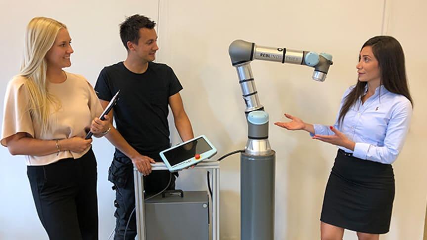 Projektledare Susanna Österlund, automationsingenjör Tommy Apelgren och projektledare Shammeran Benjamin vid en av de robotar som ska levereras till kund för att ingå i arbetslaget.
