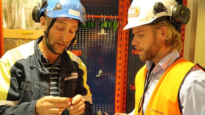 Bo Johansson från Smurfit Kappa och Erik Wikström från Abus tittar på hänglåsen i ett av kontrollrummen inne i fabriken.