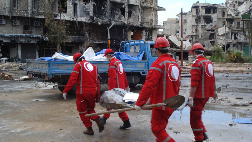 Syrian Arab Red Crescent volunteers retrieving bodies from the streets of Aleppo.