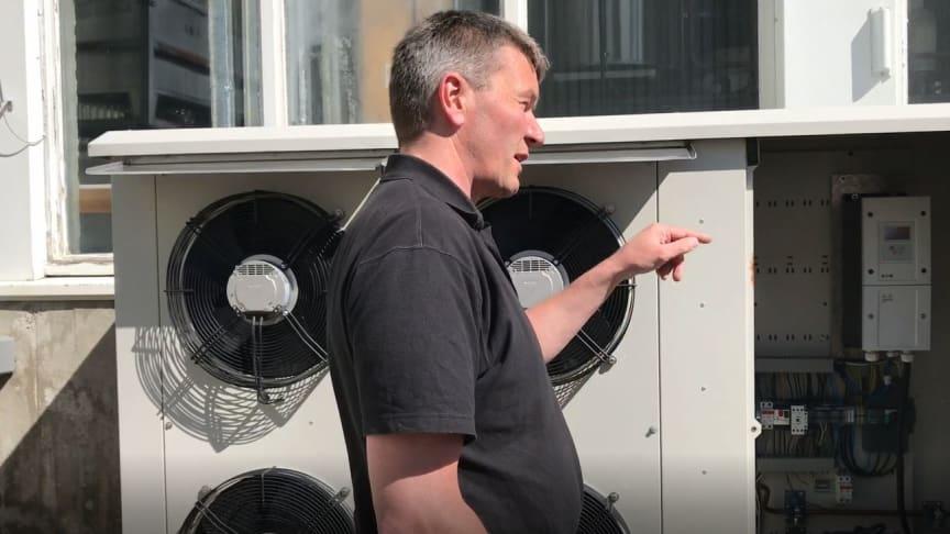 Meieribestyrer Trond Lund i Rørosmeieriet foran meieriets nye varmepumper (Skjermdump fra video).
