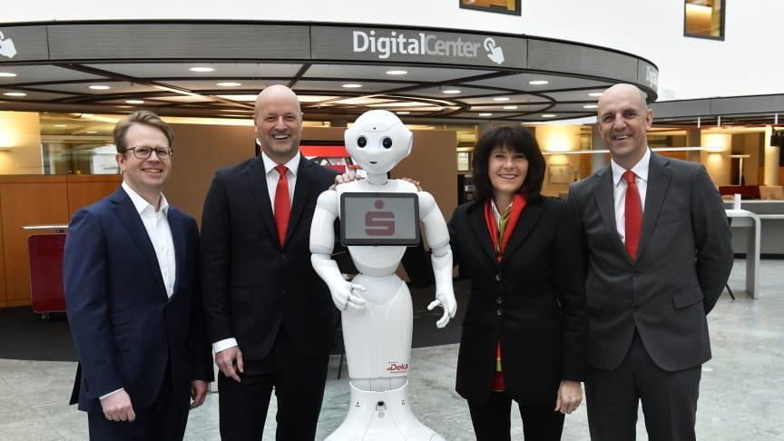 """(v.li.) Dr. Bernd Hochberger, Ralf Fleischer, Marlies Mirbeth und Stefan Hattenkofer mit Roboter """"Monaco Pepper"""" im neu eröffneten Digital-Center der Stadtsparkasse München."""
