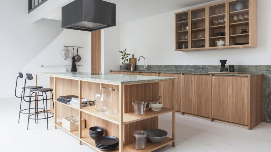 Intro med indfræsede greb og underskabe i modellen Brahe samt vitrineskabe på væggen i modellen Ramel. Træfronterne er i elmetræ og bordpladerne, der her også bruges som vægdekoration er i grøn granit.