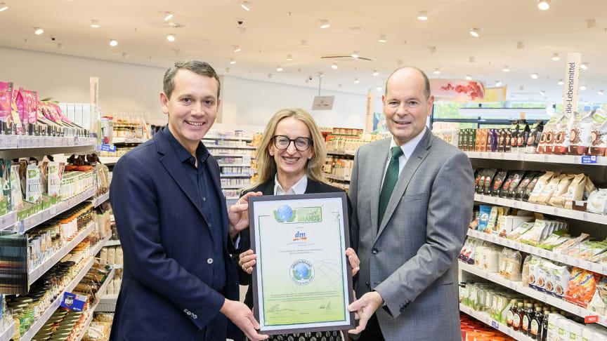 Norbert Lux (rechts), Geschäftsführer GREEN BRANDS, überreicht den dm-Geschäftsführern Kerstin Erbe (mitte) und Christoph Werner (links) das GREEN BRANDS Germany Zertifikat © dm/ARTIS-Uli Deck