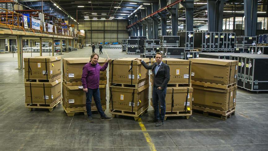 Jens Richter (links) und Jan Walter (rechts) vor den Griffyn 4K32-RGB Projektoren im Lager von publitec und NicLen