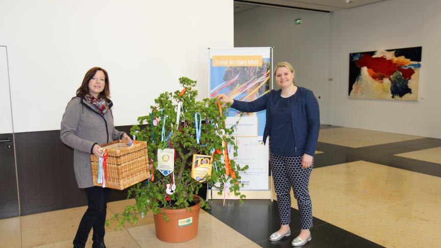 Sabine Neujahr (Lions Club Corona) und Martina Seidel (Barmenia) schmücken den Maibaum in der Barmenia