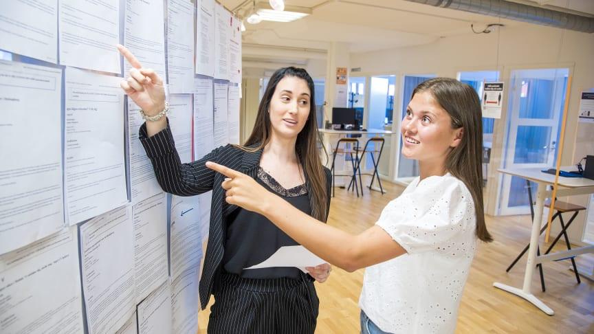 Från v. i bild: Suzana Majetic, arbetsmarknadskonsulent, och Thea Hedin står vid AME:s jobbtorg och går igenom några av morgonens nyinkomna jobb.