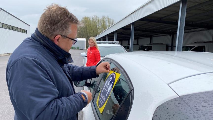 Mats Linderholm, förvaltningschef teknisk serviceförvaltning, och Emilie Ekander, enhetschef kommunikation, försåg tillsammans de första av kommunens bilar med dekalerna som ska påminna om att hålla avstånd.