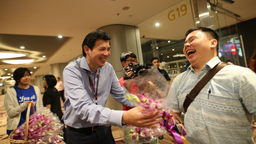 CEO of CAG Mr Lee Seow Hiang welcomes passengers arriving on T4's first arrival flight with orchids