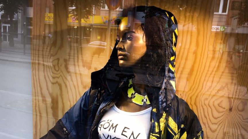 """""""Göm en flykting – om det blir olagligt, göm två"""", budskap på t-shirt i ett av Björkåfrihets skyltfönster 2018."""