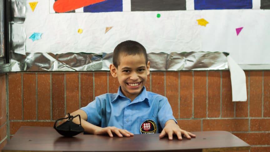 Juan Pablo, 12, från Venezuela sitter och ler vid sin skolbänk.