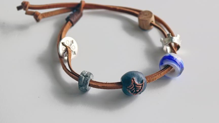 Det kompletta Pilgrimsarmbandet består av ett läderarmband med sex olika pärlor och berlocker. Såväl själva läderarmbandet som de dekorativa pärlorna/berlockerna symboliserar olika delar av natur- och kulturarvet längs Sankt Olavsleden.