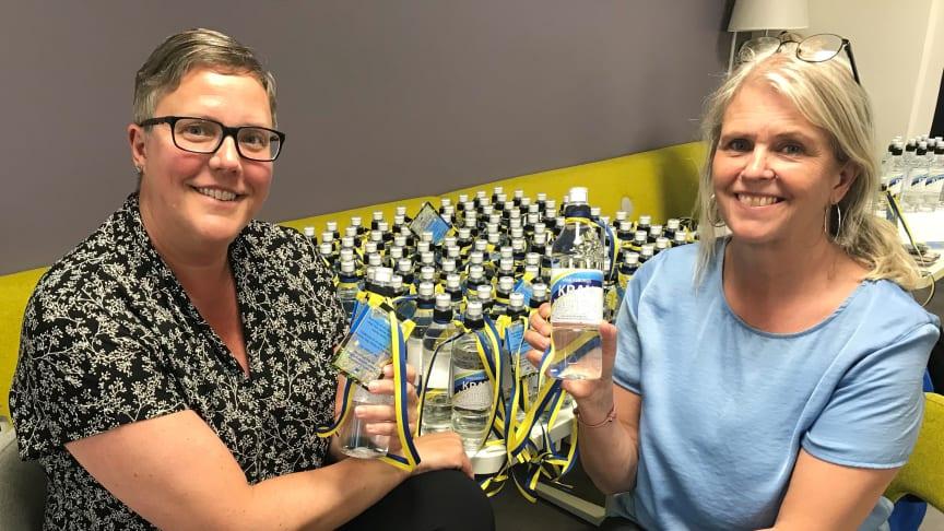 Sara Gunnarsson Forsberg och Tina Lundström, Vänersborgs kommun, visar upp vattenflaskorna som studenterna får.