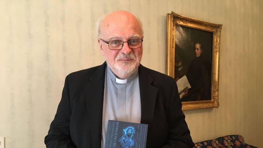 Kardinal Anders Arborelius med den katolska socialläran som nu finns i svensk översättning.