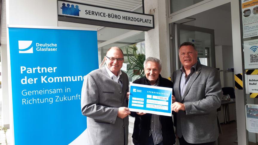 Peter Reisinger (Deutsche Glasfaser, links) übergab den symbolischen Scheck an Vereinsvorstand Gerhard Wolf (mittig) und Bürgermeister Piet Mayr.