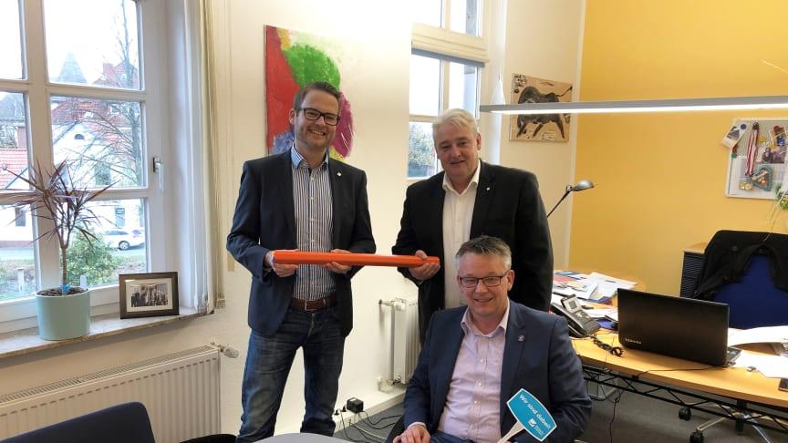 Bürgermeister Andreas Wittenberg hat einen Vertrag für einen echten, kupferfreien Glasfaseranschluss unterzeichnet. Dahinter: Tjark Hartmann (links) und Stefan Teutscher von Deutsche Glasfaser.