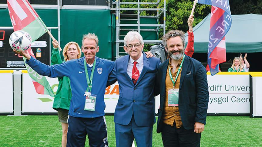Ari Huldén, Homeless World Cup -järjestön perustaja Mel Young ja edellisten kisojen lähettiläs, walesilainen näyttelijä Michael Sheen  asunnottomien jalkapallon MM-kisoissa Cardiffissa kesällä 2019.