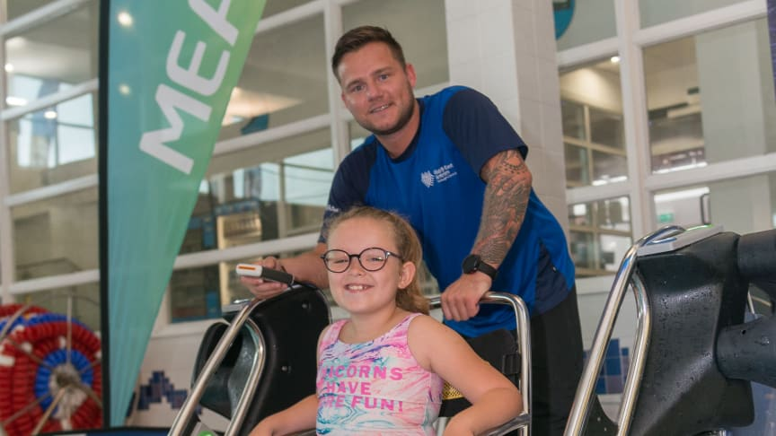 Avah McGinty, pictured with lifeguard Jason, trying out the Poolpod at Seven Towers Leisure Centre.