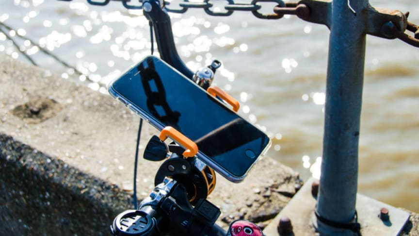 iPhone attached to bicycle handlebars by the Thames