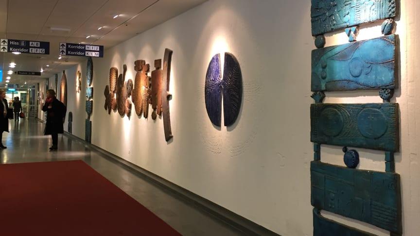 Syntolkning: Lindbergs keramiska gestaltning består av skisser i väggen och stora väggfasta objekt placerade längst en korridor i huvudentrén, Nacka sjukhus.