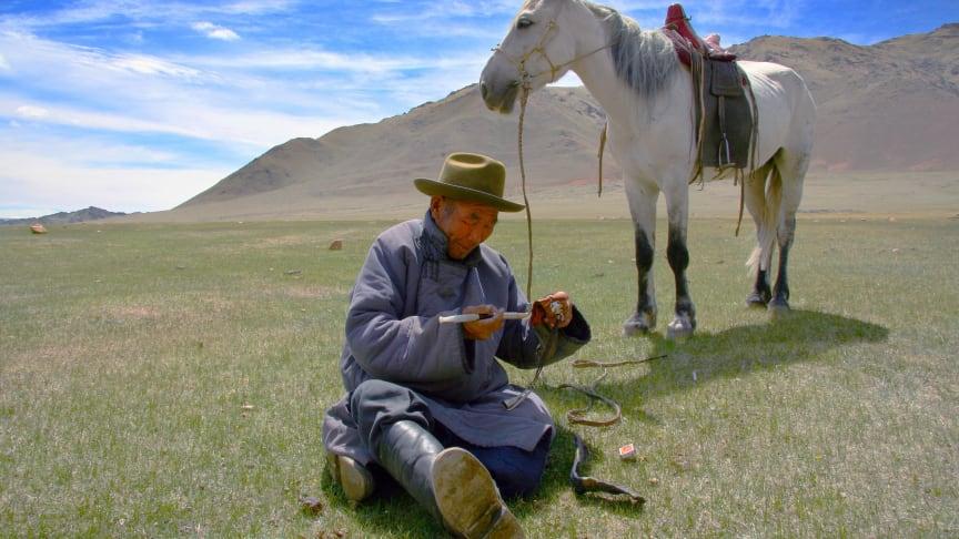 Hästburen herde med pipa, Kovd Aimag, i västra Mongoliet.