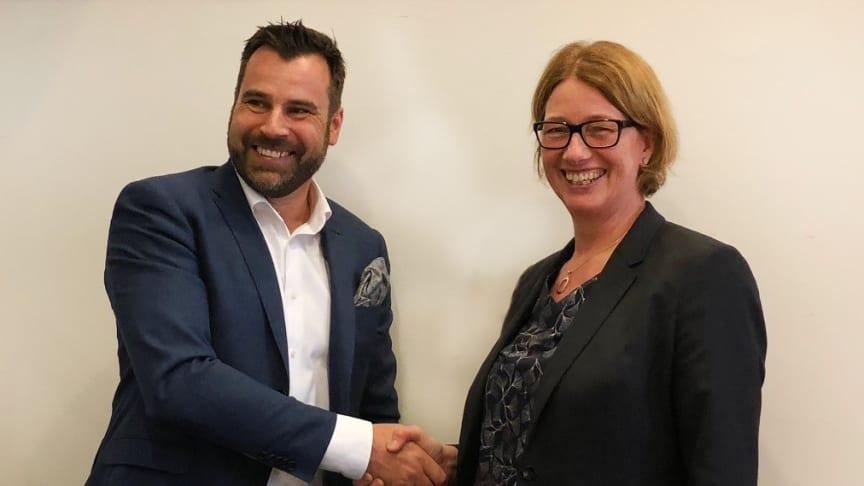 Mats Broman, affärsområdeschef, Symetri FM skakar hand med fastighetsdirektören Åsa Öttenius, fastighetskontoret, Stockholms stad i samband med att samarbetsavtalet kring nytt IT-stöd till fastighetskontoret signeras.