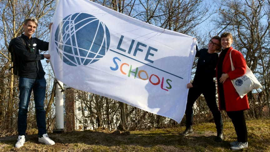 Magnus Köpman, LHU-koordinator och lärare, hissar LIFE School-flaggan tillsammans med Therese Rosenblad och Sara Jansson från LIFE Academy.