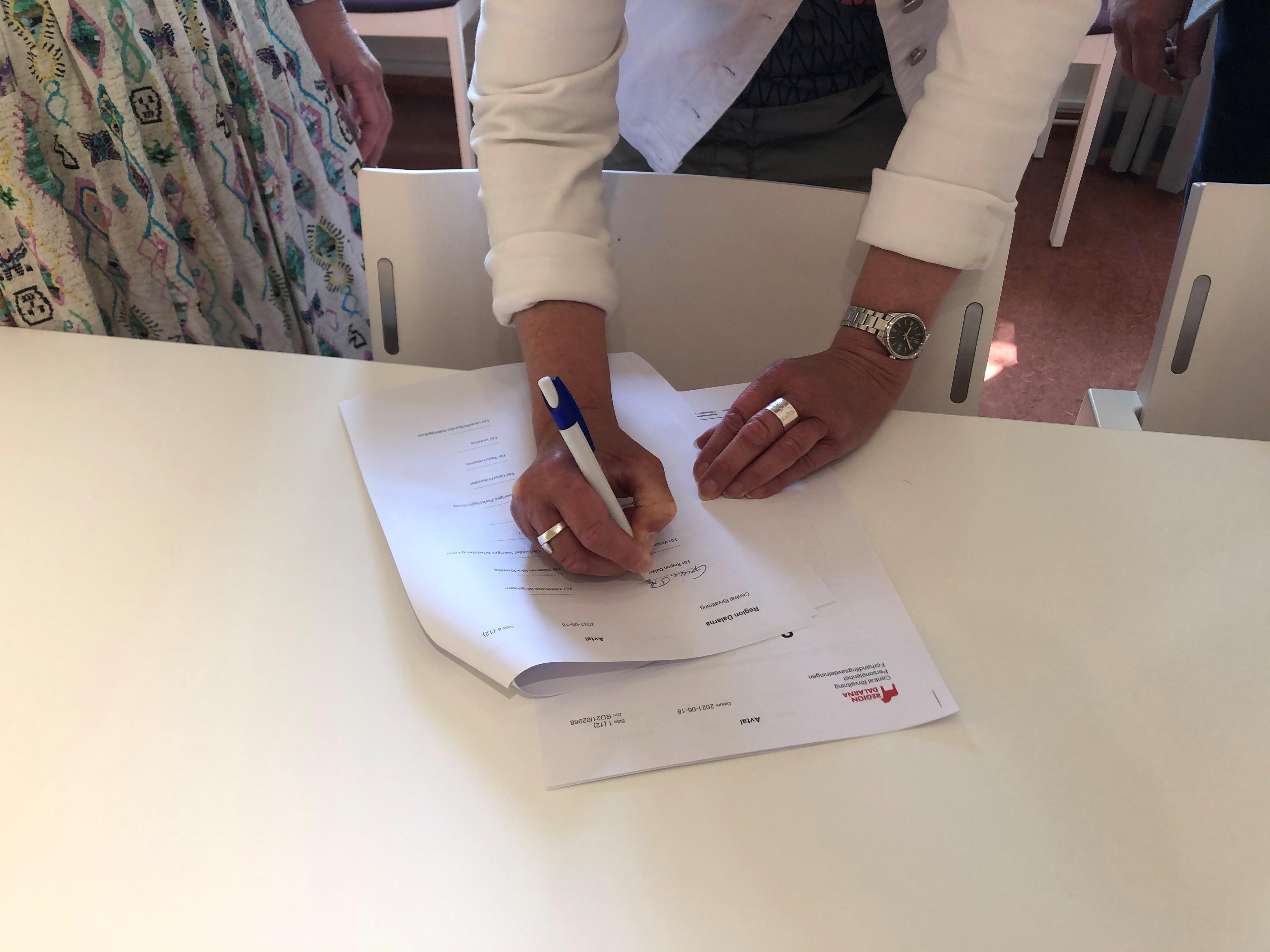 Personaldirektör Gunilla Stenback skriver på avtalet.