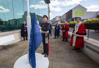Her Majesty's Lord Lieutenant of County Antrim, David McCorkell KStJ hoisting MEA Centennial Flag