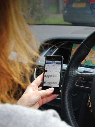 Driver using a handheld smartphone at the wheel